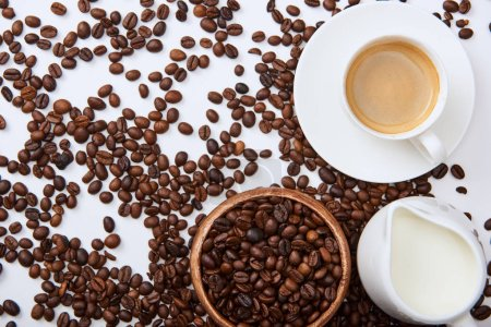 Photo for Top view of tasty coffee in cup on saucer near scattered roasted beans, wooden bowl and milk jug - Royalty Free Image