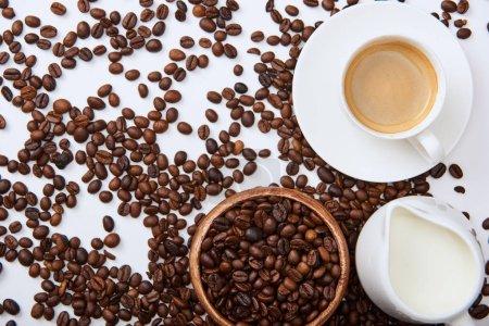 Photo pour Vue du haut du café savoureux dans la tasse sur la soucoupe près des haricots torréfiés dispersés, du bol en bois et de la cruche de lait - image libre de droit