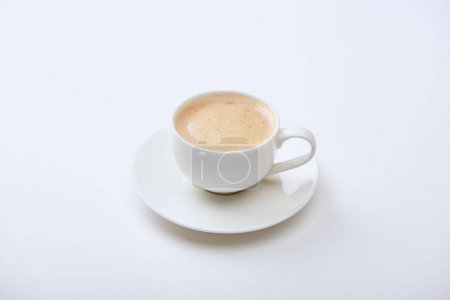 Photo for Delicious coffee with foam in cup on saucer on white background - Royalty Free Image