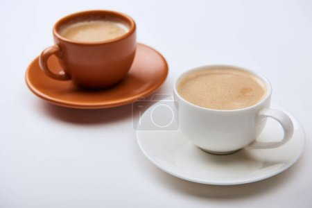 Photo for Selective focus of delicious coffee with foam in cups on saucers on white background - Royalty Free Image