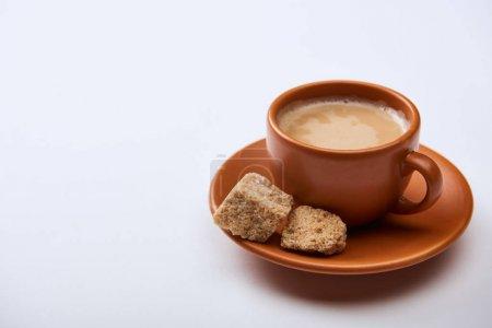 Photo pour Café savoureux avec la mousse dans la tasse sur la soucoupe près de la sucre brun sur le fond blanc avec l'espace de copie - image libre de droit
