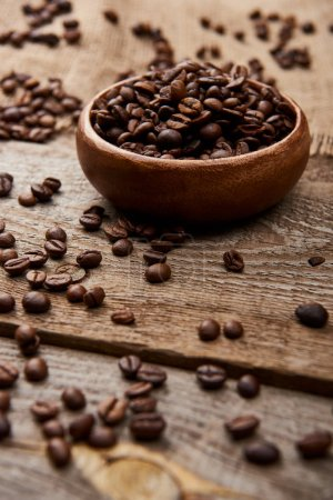 Photo for Selective focus of fresh roasted coffee beans scattered near bowl on wooden board - Royalty Free Image