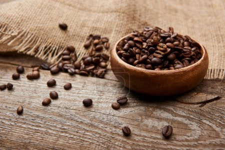 Photo pour Grains de café torréfiés frais dans le bol près du sac sur la planche en bois - image libre de droit