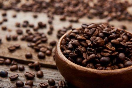 Photo pour Fermer vers le haut de la vue des grains de café torréfiés dans le bol sur la planche en bois - image libre de droit