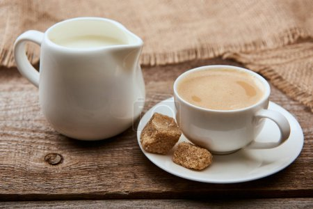 Photo for Delicious coffee with foam in cup on saucer with brown sugar near sackcloth and jug milk on wooden background - Royalty Free Image