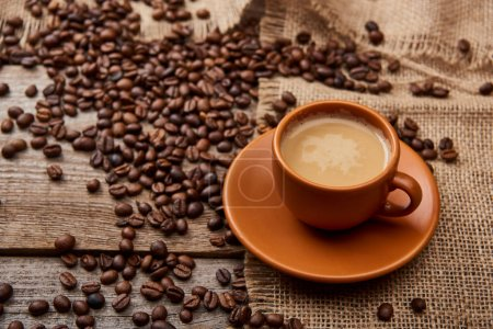 Photo for Coffee beans near cup of coffee on wooden background - Royalty Free Image