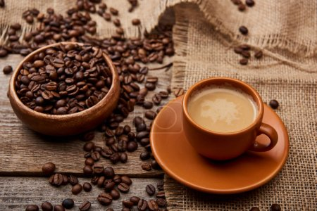 Photo for Coffee beans in bowl near cup of coffee on wooden background - Royalty Free Image