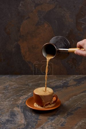 Photo for Partial view of man pouring coffee from cezve in cup on marble surface - Royalty Free Image