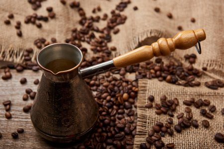 Photo for Cezve near coffee beans and sackcloth on wooden table - Royalty Free Image