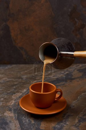 Photo for Pouring coffee from cezve into cup on marble surface - Royalty Free Image