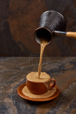Photo for Pouring coffee from cezve into cup and on saucer on marble surface - Royalty Free Image