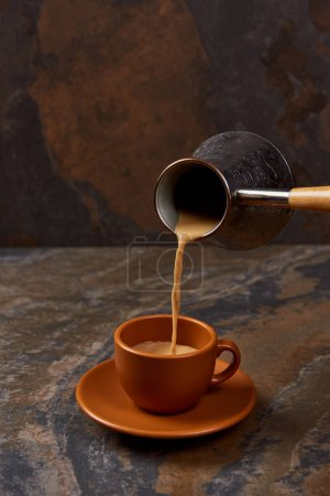 Photo for Pouring hot coffee from cezve into cup on marble surface - Royalty Free Image