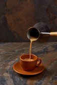 "Постер, картина, фотообои ""pouring hot coffee from cezve into cup on marble surface"""