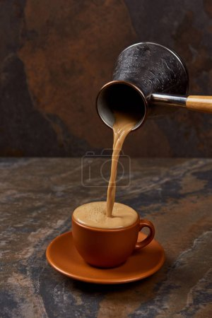 Photo for Pouring hot tasty coffee from cezve into cup on marble surface - Royalty Free Image