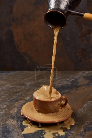 Photo for Pouring hot coffee from cezve into cup with puddle near saucer on marble surface - Royalty Free Image