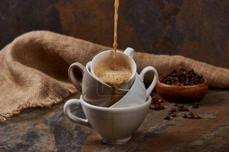 Photo pour Émettant le café chaud des tasses sur la surface de marbre près du sac et des haricots - image libre de droit