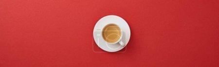 Photo pour Vue supérieure de tasse blanche avec le café frais sur la soucoupe sur le fond rouge, projectile panoramique - image libre de droit