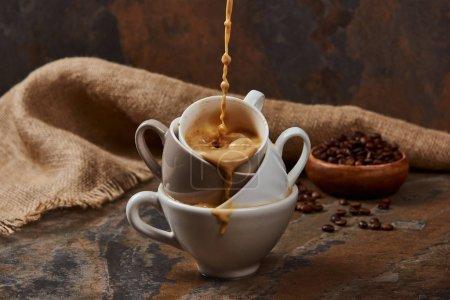 Photo pour Émettant du café chaud des tasses près du sac et des haricots - image libre de droit