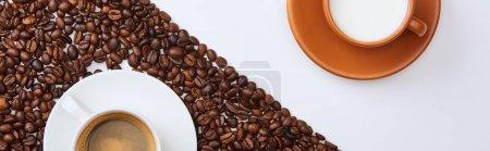 Photo pour Coup panoramique de café délicieux dans la tasse parmi les haricots torréfiés près de tasse de lait sur le fond blanc - image libre de droit