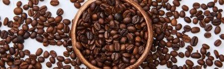 Photo pour Coup panoramique des haricots torréfiés de café dans le bol en bois sur le fond blanc - image libre de droit