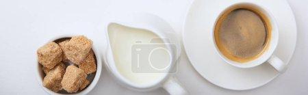 Photo pour Coup panoramique de café savoureux dans la tasse sur la soucoupe près du lait et de la cassonade sur le fond blanc - image libre de droit
