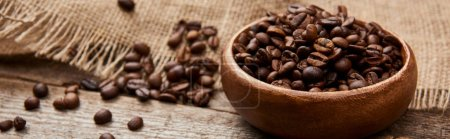 Photo for Close up view of roasted coffee beans in bowl near sackcloth on wooden board, panoramic shot - Royalty Free Image