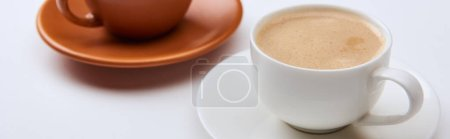 Photo pour Focus sélectif du café avec de la mousse dans des tasses sur des soucoupes sur le fond blanc, tir panoramique - image libre de droit