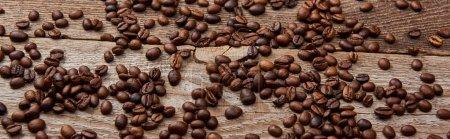 Photo pour Coup panoramique de table rustique en bois avec des grains de café torréfiés dispersés - image libre de droit