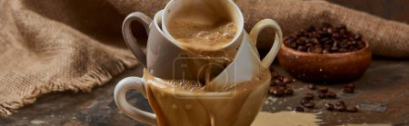Photo for Panoramic shot of flowing out hot coffee from cups on marble table near sackcloth and beans - Royalty Free Image