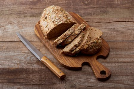 Photo for Fresh baked cut loaf of bread with seeds on wooden chopping board near knife on table - Royalty Free Image