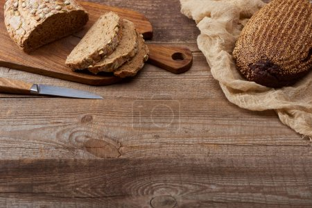 Photo for Fresh baked cut bread with seeds on chopping board near knife and bread on cloth on wooden table - Royalty Free Image
