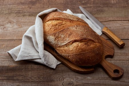 Photo for Fresh baked bread loaf in napkin near knife on chopping board on wooden table - Royalty Free Image