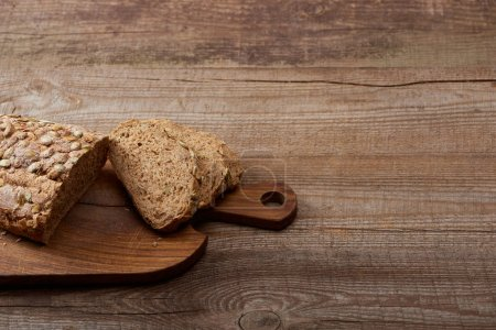 Photo for Fresh cut bread loaf on chopping board on wooden table - Royalty Free Image