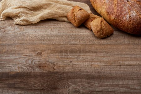Photo for Fresh bread loaf and buns near cloth on wooden table with copy space - Royalty Free Image