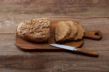 Photo for Fresh cut loaf of bread with seeds on chopping board near knife on wooden table - Royalty Free Image