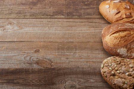 Photo for Fresh baked loaves of bread on wooden rustic table - Royalty Free Image