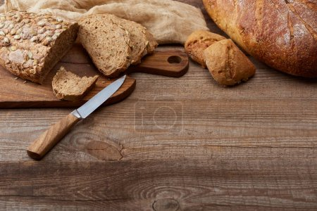 Photo for Fresh cut and whole bread loaves and buns, knife and chopping board near cloth on wooden table with copy space - Royalty Free Image