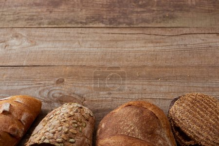 Photo for Fresh baked loaves of delicious bread on wooden rustic table - Royalty Free Image