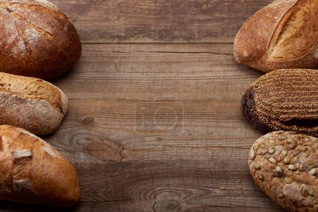Photo for Fresh baked loaves of tasty bread on wooden rustic table with copy space - Royalty Free Image