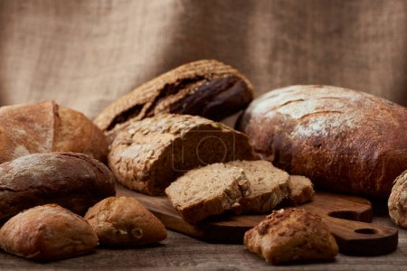 Photo for Delicious loaves of bread on wooden chopping board with sackcloth on background - Royalty Free Image