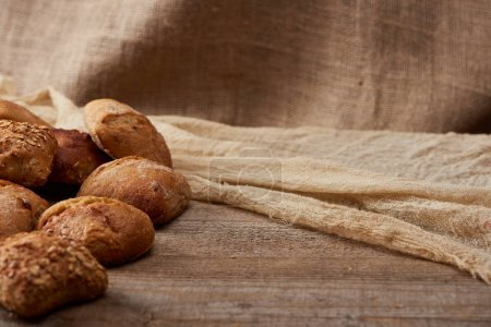 Photo for Delicious loaves of bread on wooden rustic table with sackcloth on background - Royalty Free Image