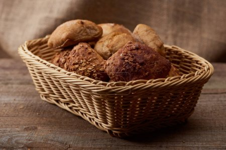 Photo for Delicious bread and buns in wicker box on wooden table - Royalty Free Image