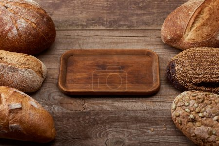 Photo for Delicious loaves of bread around empty board on wooden table - Royalty Free Image