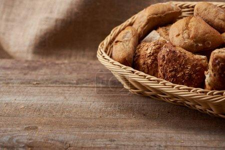 Photo pour Délicieux petits pains frais dans une boîte en osier sur une table en bois avec espace de copie - image libre de droit