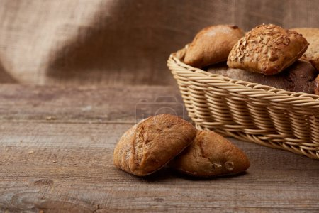 delicious fresh buns in wicker box on wooden rustic table with copy space