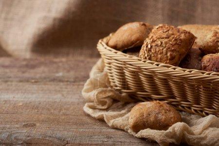 Photo pour Délicieux petits pains frais dans une boîte en osier sur table rustique en bois avec chiffon avec espace de copie - image libre de droit