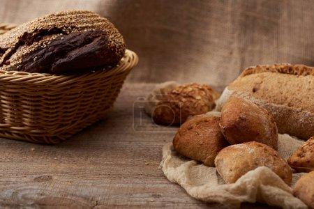 Photo pour Délicieux pains frais et pains en osier sur table rustique en bois avec tissu - image libre de droit