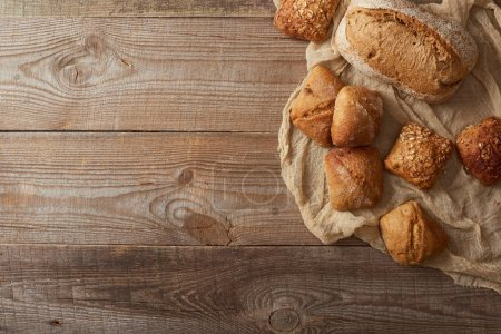 top view of fresh baked bread and buns on cloth on wooden table