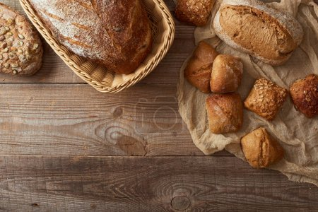 Photo for Top view of fresh baked bread in wicker basket and buns on cloth on wooden table - Royalty Free Image