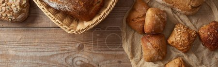 top view of fresh baked bread in wicker basket and buns on cloth on wooden table, panoramic shot